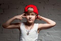 凉快的年轻Hip Hop男孩画象红色帽子和红色裤子的 免版税库存图片