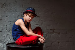 凉快的年轻Hip Hop男孩画象蓝色帽子和红色裤子的坐黑桶 免版税图库摄影