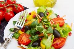 凉拌生菜用在白色板材的蕃茄在木桌上 免版税库存照片