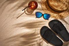凉鞋、草帽和太阳镜在含沙背景,顶视图 库存照片