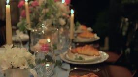 减慢欢乐桌掀动与服务,新月形面包,蜡烛,蛋白杏仁饼干,花的 股票视频