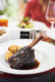 减慢煮熟的羊羔腿用被烘烤的土豆 库存照片