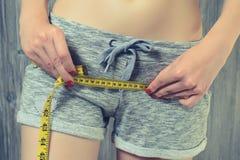减肥亭亭玉立的减重身体关心适合的健身厘米健康生活方式概念的饮食 测量她的臀部的妇女使用黄色t 库存图片