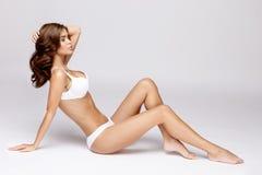 减肥在灰色背景的被晒黑的妇女的身体 库存图片