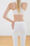 减肥摆在运动服的被定调子的妇女用在臀部的手 免版税库存图片