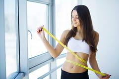 减肥测量她的有卷尺的少妇腰部 库存图片