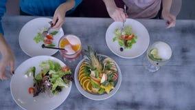 减肥的健康食品在新党,在吃晚餐和供食沙拉的年轻女人的顶视图在桌上与 股票视频