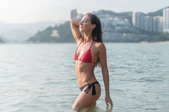 减肥站立在有她的闭上的眼睛的海的少妇佩带的比基尼泳装采取享用新鲜空气的深呼吸,温暖 免版税库存图片