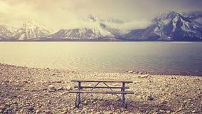减速火箭传统化了一条空的长凳有在湖的美丽的景色 免版税库存图片