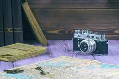 减速火箭式 旧书和一张地图在桌上 影片照相机和几枚硬币 免版税库存照片