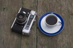 减速火箭照相机和一个杯子在桌上的无奶咖啡 免版税库存图片