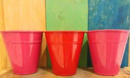 减速火箭的与五颜六色的桃红色和红色空的罐头的颜色木纹理背景 免版税库存照片