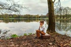 减速火箭的古板的村庄衣裳的一个年轻少年人难过坐一个老手提箱扶植了他的在河的河岸的头 库存照片