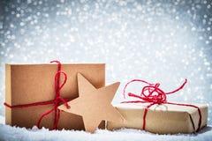 减速火箭的土气圣诞节礼物,在雪的礼物在闪烁背景 免版税库存照片