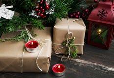 减速火箭的圣诞节礼物在与蜡烛的圣诞树下和 图库摄影