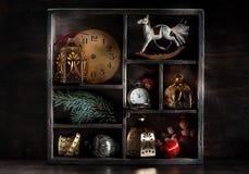 减速火箭的圣诞节装饰和玩具在一个木箱 古色古香的时钟、摇马和球 免版税库存图片