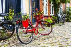 减速火箭的在鹅卵石街道上的葡萄酒红色自行车在老镇 免版税图库摄影
