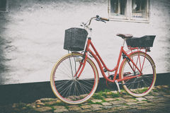 减速火箭的在鹅卵石街道上的葡萄酒红色自行车在老镇 库存图片