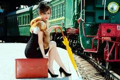 减速火箭的女孩坐手提箱在火车站。 免版税库存照片