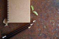 减速火箭的安置在生锈的书桌视图的笔记和铅笔由flatlay 免版税库存照片
