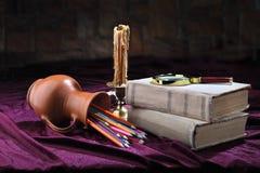 减速火箭的对象风格化看法  在桌上是:旧书、一个烛台、一个蜡烛、色的铅笔在一个被翻转的水罐和上午 库存照片