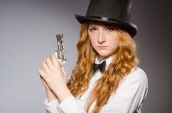 戴减速火箭的帽子和拿着武器的俏丽的女孩 免版税库存照片