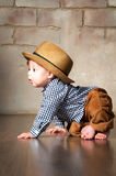 减速火箭的帽子和条绒长裤的学会Llittle的男孩爬行在所有fours的地板上 库存照片