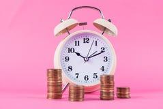 减速火箭的手表和硬币在桃红色背景 免版税库存照片