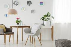 减速火箭的扶手椅子,桌,枝形吊灯,陶瓷墙壁装饰和 免版税图库摄影