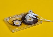 减速火箭的技术 塑料透明卡型盒式录音机和白色真空耳机在明亮的黄色背景 库存照片