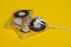 减速火箭的技术 塑料透明卡型盒式录音机和白色真空耳机在明亮的黄色背景 库存图片