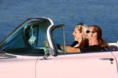 减速火箭的新夫妇在桃红色卡迪拉克中 免版税库存照片