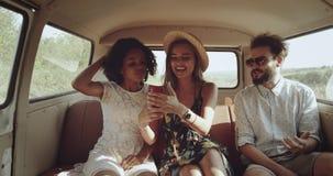减速火箭的时髦的朋友、两个完善的女孩有美好的微笑的和一个人在途中在通过看减速火箭的公共汽车上 影视素材