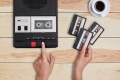 减速火箭的材料,老项目,记忆 交换在老磁带记录器和拿着三个卡式磁带的手选择歌曲 图库摄影