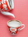 减速火箭的杯子和茶壶有红色样式的在桌布与圆点 顶视图 库存图片