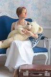 减速火箭的样式婚礼礼服的女孩拿着一头玩具熊,说去 免版税库存照片