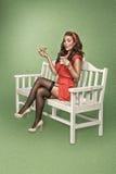 减速火箭的样式的女孩喝与蛋糕的茶 免版税库存照片