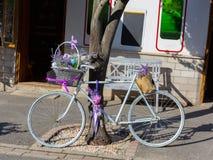 减速火箭的样式蓝色自行车用淡紫色开花作为创造性的装饰在舒适小街道的商店附近 库存照片