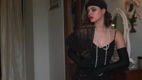 减速火箭的样式,一件黑礼服的少妇有一条美丽的项链的拿着一个爱好者 股票视频