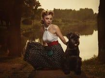 减速火箭的样式 有一条狗的女孩在日落的一个公园发出光线 免版税库存图片