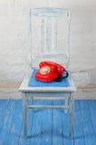 减速火箭的样式-红色葡萄酒电话,老椅子 免版税库存图片