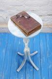 减速火箭的样式-葡萄酒圣经和玻璃在一个老花架 免版税库存图片