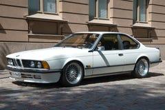 减速火箭的汽车炫耀小轿车在城市街道上的BMW E24白色 芬兰土尔库 库存图片