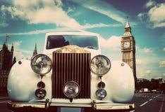 减速火箭的汽车,在大本钟,伦敦,英国旁边的大型高级轿车 库存照片