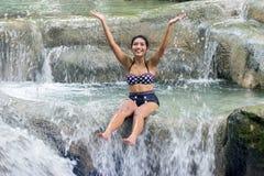 减速火箭的泳装的妇女嬉戏在瀑布 免版税库存图片