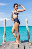 减速火箭的泳装致敬的妇女在码头 图库摄影