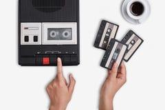 减速火箭的热的咖啡站立白色表面上的录音机、卡式磁带和杯子 交换在盒式磁带录音机改变的手 免版税库存图片