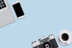 减速火箭的照相机、现代便携式计算机、巧妙的说谎在蓝色平的backround的电话和咖啡 在fla的现代和减速火箭的供应 免版税库存照片