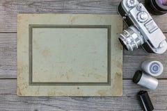 减速火箭的照相机、透镜、底片和老纸在木sur 库存照片