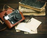 减速火箭的照相机和一些老照片在木桌背景 免版税图库摄影